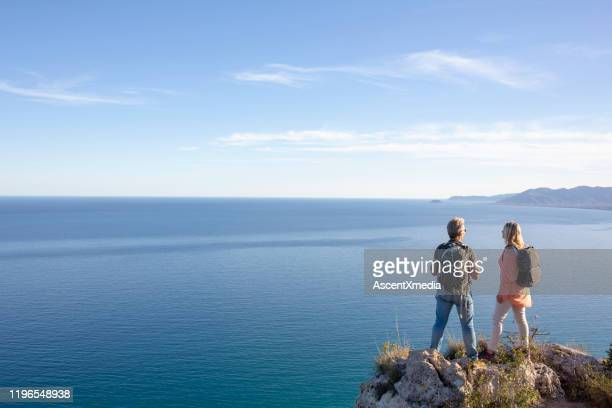 mature hikers stand on rock outcrop in mountains above the sea - mediterranean sea stock pictures, royalty-free photos & images