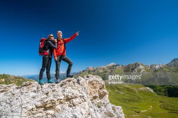 mature hiking couple happy to be outdoors together in amazing alpine mountain landscape - vita attiva foto e immagini stock