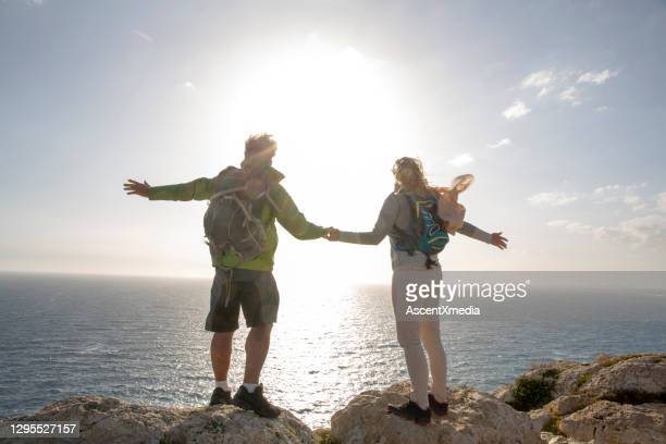 mature hiking couple look out over coastline in the morning - look back at early colour photography imagens e fotografias de stock