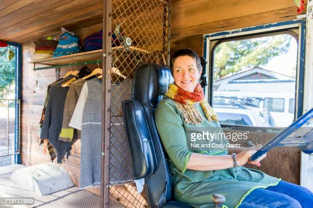 Mature hippy woman in driving seat of camper van