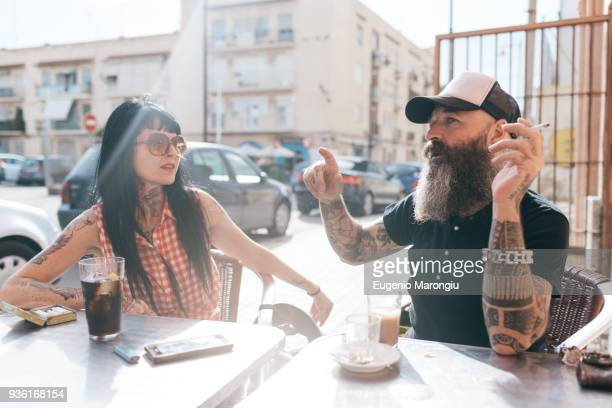 Mature hipster couple chatting at sidewalk cafe, Valencia, Spain