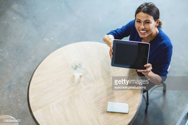 mature hispanic adult female corporate office work using technology - eyecrave  stock pictures, royalty-free photos & images