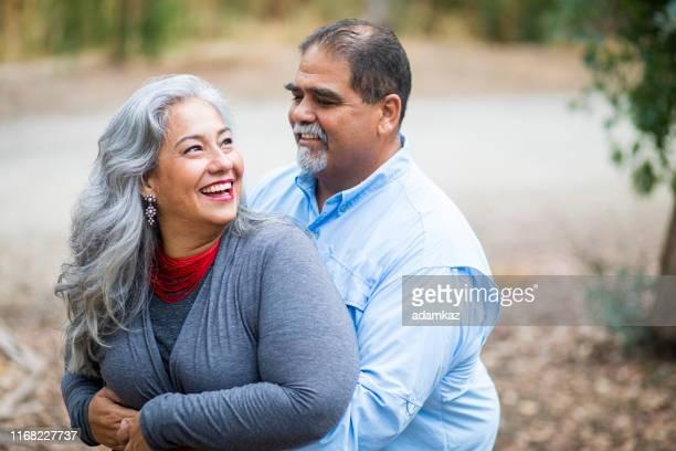 ein reifes hispanisches paar flirtet im freien - herbst winter kollektion stock-fotos und bilder