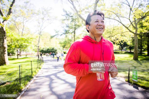 mature hispanic man jogging in central park - sweatshirt stock pictures, royalty-free photos & images