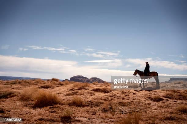 l'homme hispanique mûr monte son cheval par le désert accidenté dans l'arizona nordique près du parc tribal de vallée de monuement dans le pays indien - apache photos et images de collection