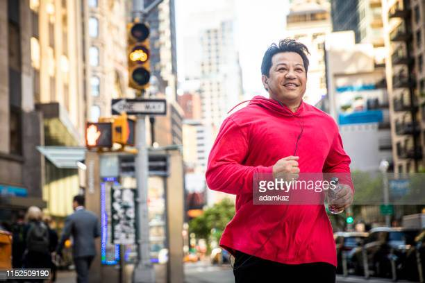mature hispanic man running in city - chubby stock pictures, royalty-free photos & images