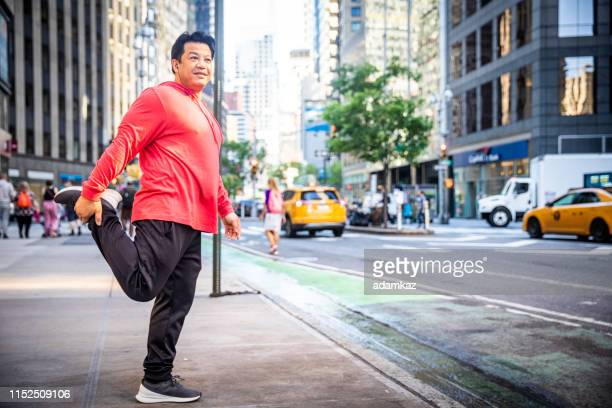 mature hispanic man stretching in city - prostate gland stock pictures, royalty-free photos & images
