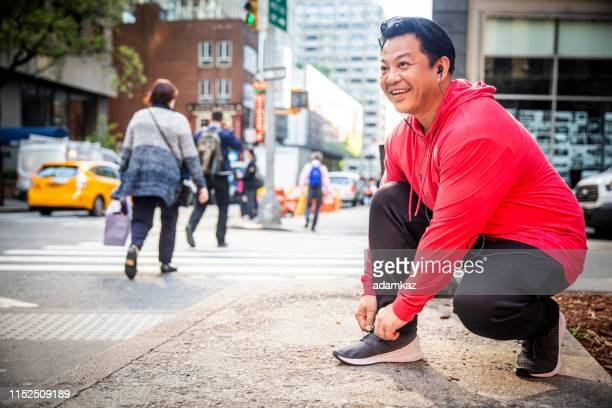 mature hispanic man tying shoe during workout in city - handsome native american men stock pictures, royalty-free photos & images