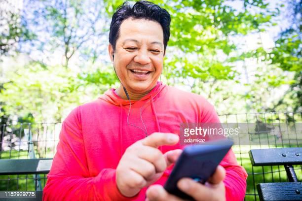homem latino-americano maduro que usa o telefone em central park - central park manhattan - fotografias e filmes do acervo