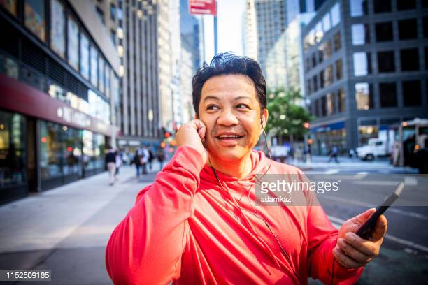 mature hispanic man using smartphone during workout - handsome native american men stock pictures, royalty-free photos & images