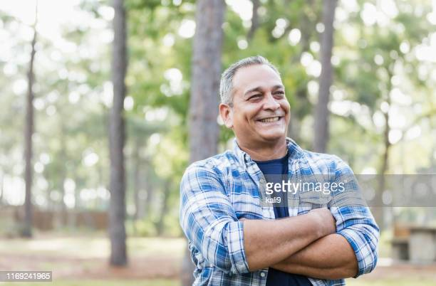 mature hispanic man wearing plaid shirt - men stock pictures, royalty-free photos & images