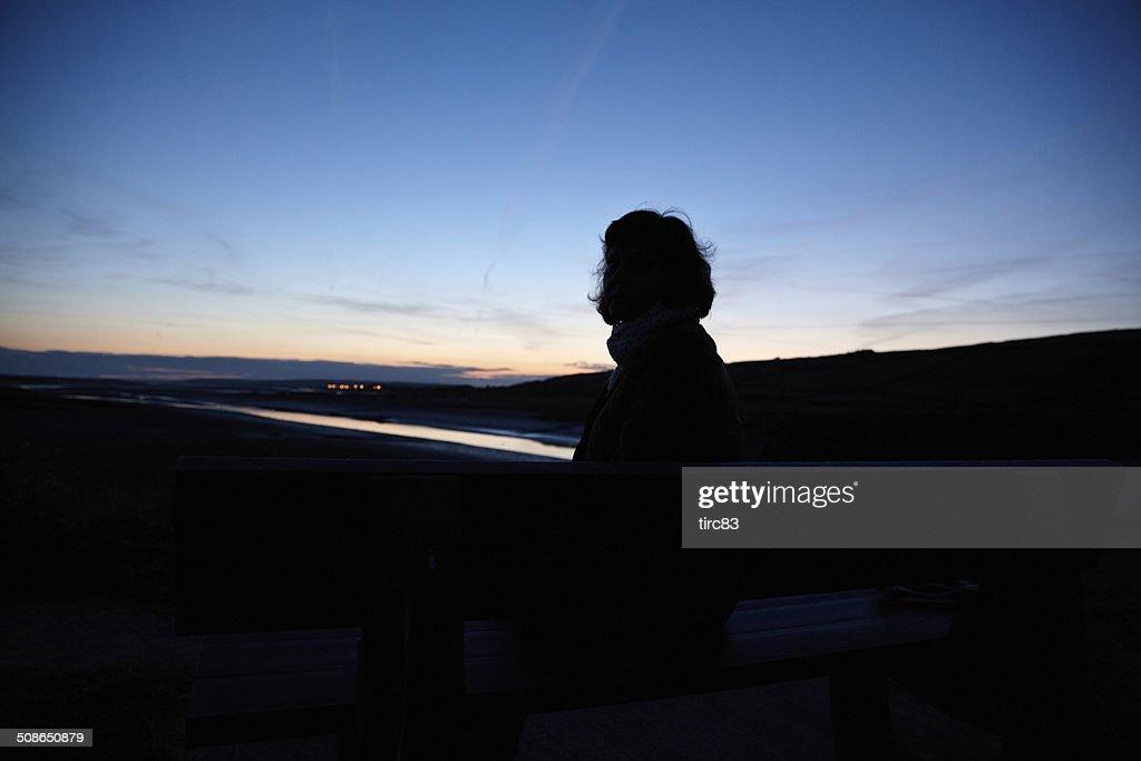 Mature hispanic woman in silhouette at sunset : Stock Photo