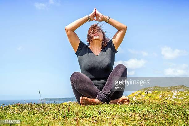 Ältere hispanic Frau Entspannende yoga-Übungen Landspitze an der Küste