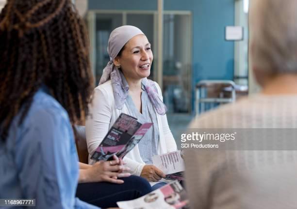 mature hispanic woman shares during breast cancer support group - cancer illness imagens e fotografias de stock