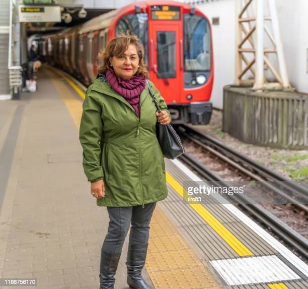 mature hispanic woman smiling on subway platform - editorial stock pictures, royalty-free photos & images