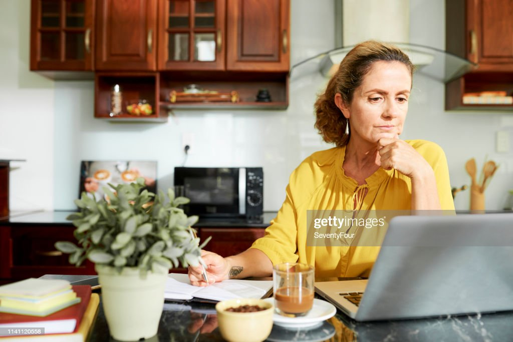 Mature housewife working on laptop : Stock Photo