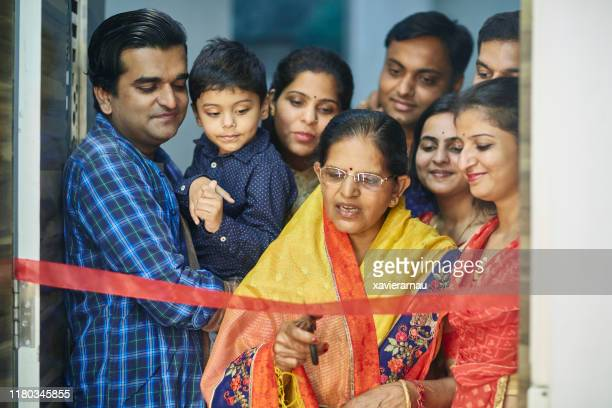 mature indian woman cutting ribbon at entrance to new home - ribbon cutting stock pictures, royalty-free photos & images