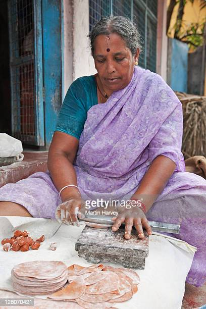 mature indian woman (58 years old) in traditional purple sari making chapati's kochi, kerala, india - 55 59 years stock pictures, royalty-free photos & images