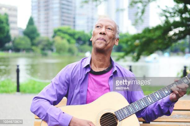 mature individual playing the guitar at a park - gender fluid stock pictures, royalty-free photos & images