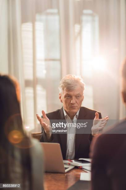 Mature insurance agent talking to a couple in the office.