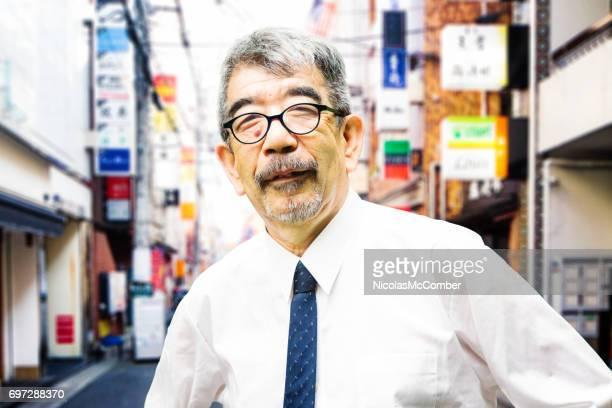 メガネ神戸で自慢している陽気な肖像画を身に着けている成熟した日本人のビジネスマン - 神戸市 ストックフォトと画像