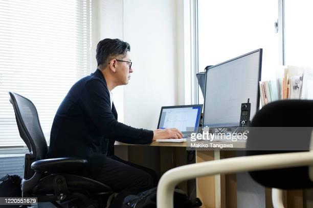 mature japanese business man working in his office - デスクトップ型パソコン ストックフォトと画像