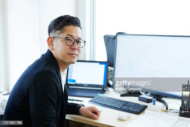 mature japanese business man working in his office - creative director stock pictures, royalty-free photos & images