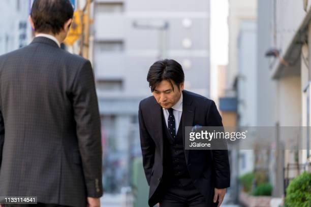 尊敬を示すためにお辞儀をする成熟した日本のビジネスマン - お辞儀 ストックフォトと画像