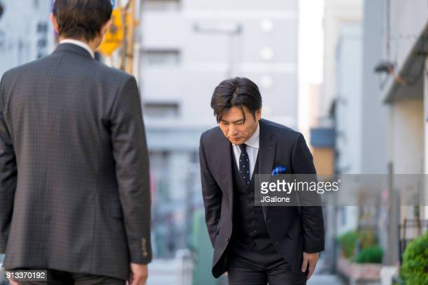 mature japanese businessman bowing to show respect - jgalione stock pictures, royalty-free photos & images