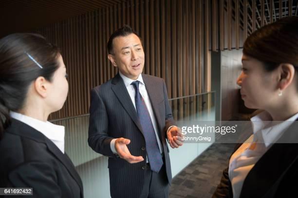 成熟した日本のビジネスマン 2 人の女性同僚に説明します。