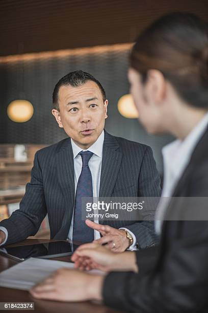 Mature Japanese businessman having discussion with female colleague