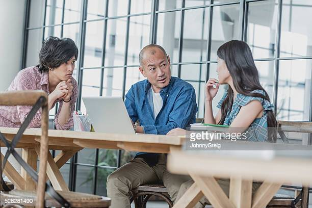 Mature Japanese businessman in meeting with colleagues