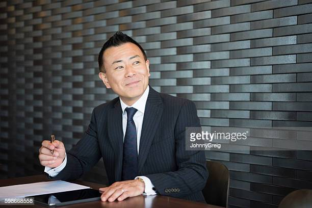 Mature Japanese businessman making notes, looking away