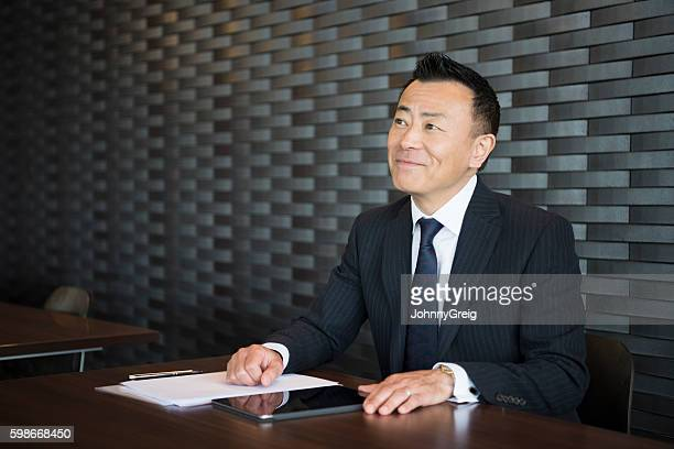 Mature Japanese businessman smiling at desk with paperwork