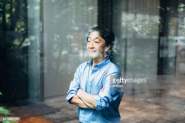 Mature Japanese businessman standing near glass in office