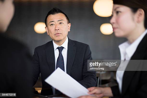 Mature Japanese businessman with female colleagues