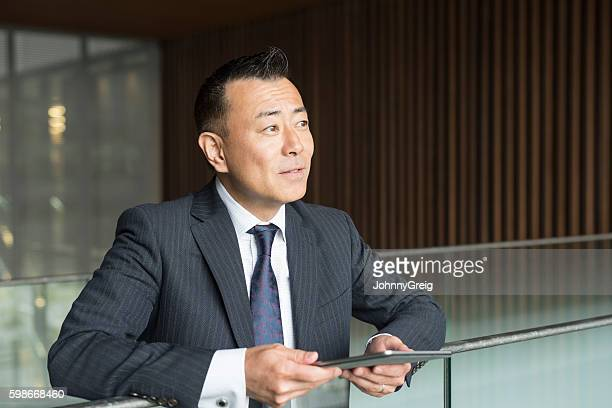 Mature Japanese businessman with tablet, looking away