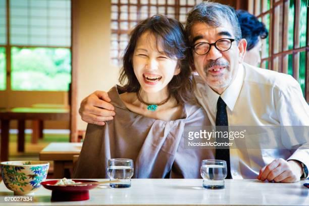 成熟した日本人夫婦の幸せな受け入れと京都のレストランで肖像画を笑って