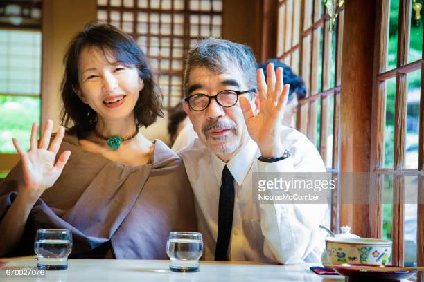Mature Japanese couple happy waving portrait in Kyoto Restaurant