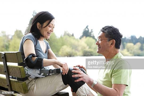 mature japanese couple putting on kneepads. - caneleira roupa desportiva de proteção imagens e fotografias de stock