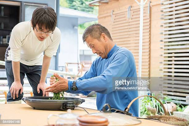 マチュア日本の父親指導の息子をロールたての紅茶 - 郷土料理 ストックフォトと画像