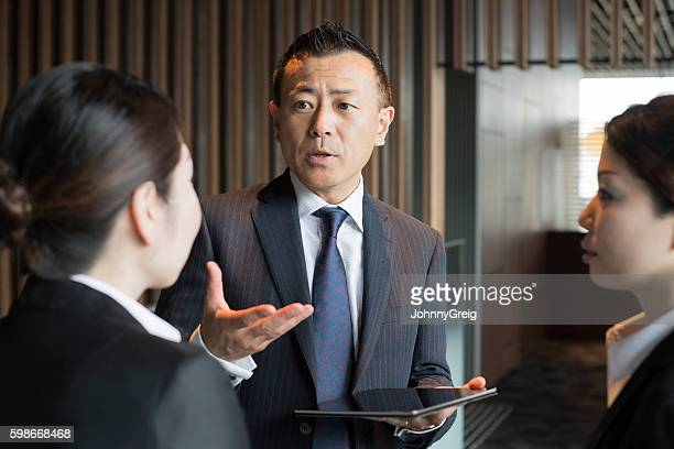 Mature Japanese male manager talking to female staff