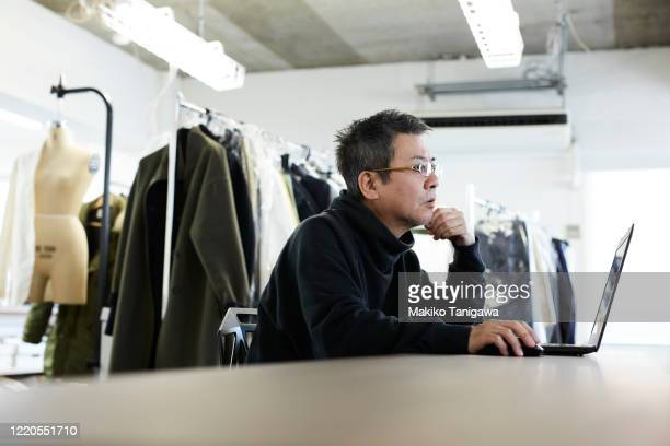 mature japanese man at apparel maker's design office - business ストックフォトと画像