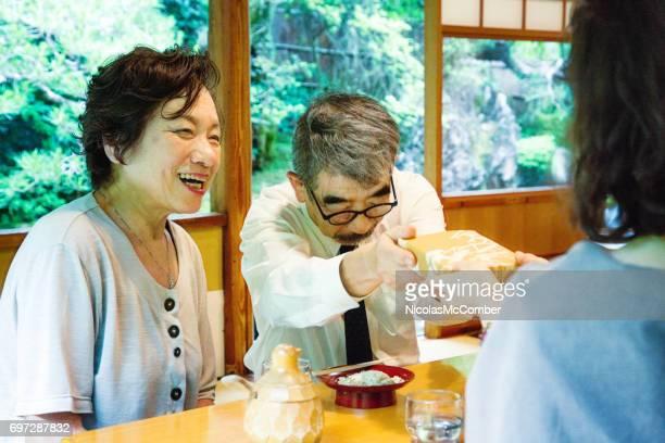 Mature Japanese man gives gift with humility at social gathering