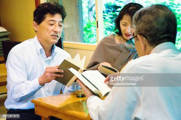 Mature Japanese man reads passage at book club in Kyoto restaurant