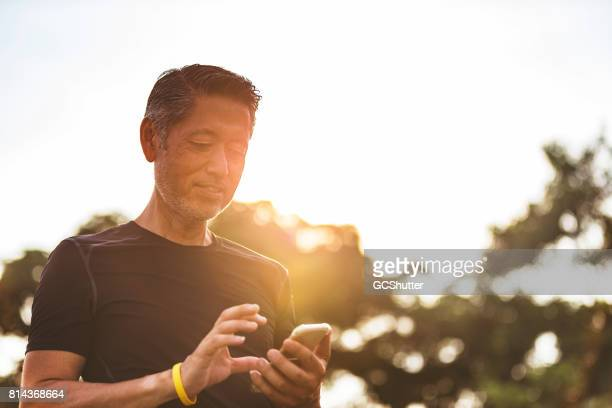 mature japanese man using his smart phone early in the morning during his walk - convenience stock photos and pictures