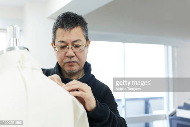 mature japanese man working in fashion industry - sewing stock pictures, royalty-free photos & images