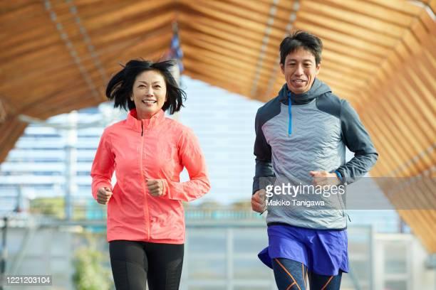 mature japanese sportsman and sportswoman running on track - スポーツ  ストックフォトと画像