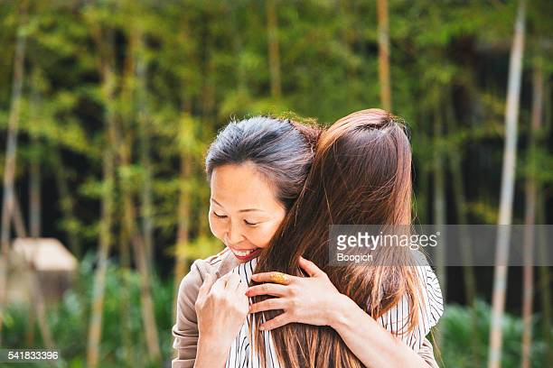 Mature Japanese Woman Hugs Daughter Outdoors in Kyoto Japan