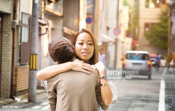 成熟した日本人女性京都通りで若い友人を抱擁します。